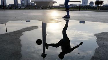 Seorang warga mengontrol bola saat olahraga sepak bola. (Bola.com/M. Iqbal Ichsan)