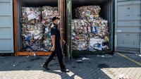 Petugas Bea Cukai Tanjung Perak berjalan melewati kontainer berisi sampah asal Australia di Pelabuhan Tanjung Perak, Surabaya, Jawa Timur, Selasa (9/7/2019). Delapan kontainer sampah seberat 210 ton tersebut diimpor PT MDI dari Australia. (JUNI KRISWANTO/AFP)