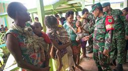 Komandan satuan tugas medis angkatan darat Indonesia Asep Setia Gunawan (kanan) mengunjungi sebuah klinik lokal di desa Ayam, distrik Asmat, di provinsi Papua Barat (26/1). (AFP/Bay Ismoyo)