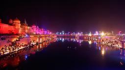 Cahaya lampu dari tanah liat menerangi tepi Sungai Sarayu sebagai bagian dari perayaan Diwali di Ayodhya, , Selasa (6/11). Kota di utara India itu memecahkan rekor dunia Guinness setelah menyalakan 300.150 lampu selama 45 menit. (AP/Rajesh Kumar Singh)
