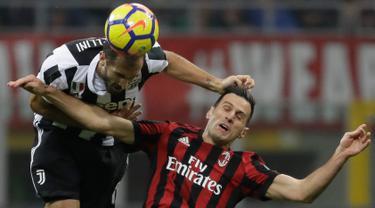 Pemain Juventus, Giorgio Chiellini menyundul bola dari pemain AC MIlan, Nikola Kalinic pada lanjutan Liga Italia di Stadion San Siro, Milan, Sabtu (28/10). Gonzalo Higuain memborong gol kemenangan saat Juventus mempermalukan Milan 2-0. (AP/Luca Bruno)