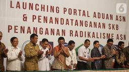 Menkominfo Johnny G. Plate (kelima kiri) bersama sebelas Kementerian dan lembaga negara  usai penandatangan kerja sama pembuatan portal aduan untuk aparatur sipil negara (ASN), Jakarta, Selasa (12/11/2019). Portal ini bisa melaporkan ASN yang diduga terpapar radikalisme. (Liputan6.com/Faizal Fanani)