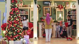 Pengunjung berfoto bersama keluarga dengan dekorasi Natal di atrium Lippo Mall Puri, Jakarta Barat, Sabtu (19/12/2020). Dominasi warna merah dan pohon cemara berhias lampu meriahkan sambut Hari Raya Natal dan Tahun Baru di atrium 1 dan 2. (Liputan6.com/Fery Pradolo)