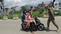 Petugas Satpol PP memberhentikan pengendara motor saat melintasi Pos Pengawasan Larangan Mudik di Cigombong, Bogor, Rabu (29/4/2020). Polres Bogor terus melakukan penyekatan  mencegat pemudik sekaligus PSBB mengantsipasi penyebaran virus Covid-19. (merdeka.com/Arie Basuki)