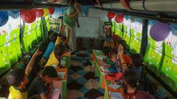 Anak-anak Suriah mengikuti pelajaran di dalam bus yang dikonversi menjadi ruang kelas di desa Hazano di barat laut Suriah (15/9/2019). Pelajaran di kelas bus ini yaitu bahasa Arab, matematika, sains, dan kadang-kadang bahasa Inggris , serta menyanyi dan menggambar. (AFP Photo/Aaref Watad)