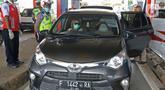 Petugas memeriksa kendaraan yang memasuki Jakarta pada penerapan PSBB di gerbang pintu Tol Pasar Rebo 2, Jakarta, Jumat (10/4/2020). Petugas kepolisian mengimbau kepada seluruh pengendara dan penumpang agar mengenakan masker. (Liputan6.com/Herman Zakharia)