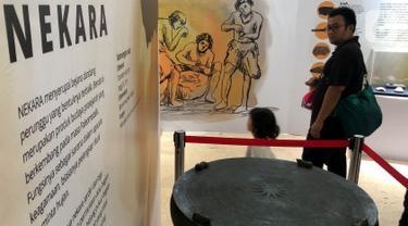 Pengunjung melihat bejana dandang perunggu pada pameran Asal Usul Orang Indonesia (ASOI) di Museum Nasional Jakarta, Minggu (3/11/2019). ASOI merupakan pameran yang menampilkan fase perkembangan manusia purba mulai dari Homo Erectus Tipik hingga Homo Sapiens. (Liputan6.com/Fery Pradolo)