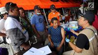 Petugas bio farma berbincang dengan warga korban gempa di kantor Dinkes Palu, Sulawesi Tengah, Minggu (7/10). Kemenkes dan Bio Farma mengirimkan 7 petugas medis yang akan bekerja selama 9 hari. (Liputan6.com/Fery Pradolo)