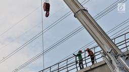 Aktivitas pekerja menyelesaikan proyek LRT Jabodebek di kawasan Cibubur, Jakarta, Senin (18/2). Tarif flat untuk moda transportasi massal ini ditetapkan setelah mendapat kepastian subsidi dari pemerintah. (Merdeka.com/Iqbal S. Nugroho)