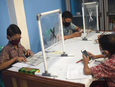 Sejumlah siswa mengikuti pembelajaran jarak jauh (PJJ) di Balai Warga RT 05/RW 02 Kelurahan Galur, Johar Baru, Jakarta, Selasa (15/8/2020). Fasilitas internet gratis diharapkan bisa membantu para siswa SD, SMP dan SMA selama pandemi Covid-19. (Liputan6.com/Fery Pradolo)