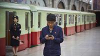 Seorang penduduk menggunakan smartphone di sebuah stasiun (Sumber: Nextshark)