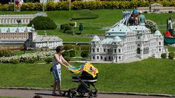 Pengunjung sambil mendorong kereta bayi melihat miniatur Wina Belvedere Palace di Taman Minimundus, Klagenfurt, Austria, Senin (8/8). Sekitar 150 model bangunan unik dari berbagai belahan dunia dipamerkan di Taman Minimundus. (REUTERS / Heinz-Peter Bader)