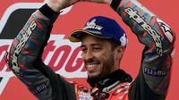 Pebalap Ducati, Andrea Dovizioso merayakan kemenangan di podium usai balapan MotoGP Grand Prix Valencia di arena balapan Ricardo Tormo, Cheste, Minggu (18/11). Andrea memenangkan balapan untuk keempat kalinya di 2018. (Javier Soriano/AFP)
