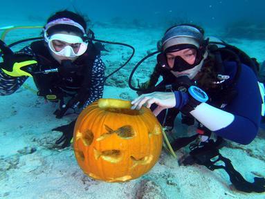 Dua penyelam, Sophie Costa dan Allison Candelmo menunjukkan buah labu dalam Kontes Mengukir Labu Bawah Air, di Cagar Alam Laut Nasional Florida Keys, Florida, Minggu (14/10). Kompetisi diadakan di laut sedalam 9 meter. (Frazier Nivens/various sources/AFP)