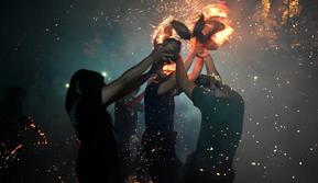 Sejumlah pemuda berpartisipasi dalam upacara perang api, yang secara lokal dikenal sebagai Siat Geni, di sebuah kuil di Tuban dekat Denpasar, Bali (13/10/2019). Dalam pementasannya, para peserta perang menggunakan baju hitam, kamen, serta mengenakan udeng di kepalanya. (AFP Photo/Sonny Tumbelaka)