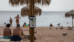 Pengisi daya bertenaga surya terpasang pada payung di pantai dekat Balai Kota Vari-Voula-Vouliagmeni, Yunani, Selasa (21/7/2020). Puluhan payung di pantai tersebut dilengkapi sistem panel surya dan port USB untuk menyediakan pengisian daya gratis dan ramah lingkungan. (Xinhua/Lefteris Partsalis)
