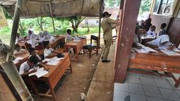 Sejumlah murid SDN Mutiara mengikuti aktivitas belajar di dalam tenda darurat di Kampung Pasir Bayur, Cibeber II, Bogor, Selasa (3/4). Di sekolah itu, hanya tersisa 2 ruangan yang dipergunakan bagi kelas 6 dan ruangan guru. (Merdeka.com/Arie Basuki)