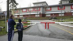 Warga melihat Sekolah Dasar Cambridge yang ditutup karena wabah COVID-19 di Surrey, British Columbia, Kanada (15/11/2020). Kasus baru COVID-19 di Kanada terus meningkat dan beberapa provinsi di negara itu telah memecahkan rekor jumlah kasus COVID-19. (Xinhua/Liang Sen)
