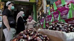 Pedagang kurma melayani pembeli di Pasar Tanah Abang, Jakarta, Rabu (22/4/2020). Pandemi COVID-19 membuat lesu penjualan kurma, keuntungan pedagang menurun hingga 80 persen lebih padahal pada tahun sebelumnya menjelang Ramadan biasanya ramai pembeli. (Liputan6.com/Johan Tallo)