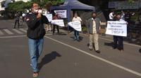 Sejumlah pedagang pasar di Kota Bandung menggelar aksi unjuk rasa di depan Pasar Baru menolak wacana perpanjangan PPKM darurat, Jumat (16/7/2021). (Liputan6.com/Huyogo Simbolon)