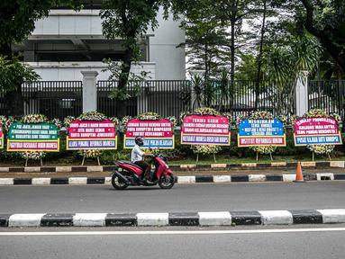 Pengendara melintasi karangan bunga di depan Gedung Kejaksaan Agung RI, Jakarta, Selasa (27/10/2020). Karangan bunga berasal dari korban terdampak kasus asuransi Jiwasraya yang mengharapkan kasus mega skandal itu bisa segera tuntas dan memberikan keadilan bagi mereka. (Liputan6.com/Faizal Fanani)