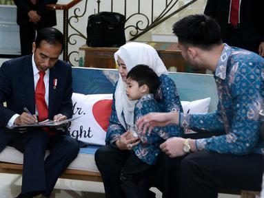 Presiden Joko Widodo memberikan tanda tangan saat berkunjung ke kediaman almarhum Raden Mas Haryo Heroe Syswanto Ns Soerio Soebagio atau yang lebih dikenal dengan nama Sys NS di Kawasan Kemang, Jakarta (2/2). (Liputan6.com/Pool/Biro Pers Setpres)