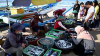 Pedagang melayani pembeli di pasar ikan di Kedonganan, Denpasar, Bali (17/10/2019). Desa Kedonganan terkenal dengan sektor Perikanan, dan juga Pantai Kedonganan yang indah. (AFP Photo/Sonny Tumbelaka)
