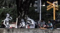 Sejumlah manusia silver bersiap untuk mencari uang di lampu merah kawasan Manggarai, Jakarta, Minggu (18/10/2020). Institute for Development of Economics and Finance (Indef) memproyeksikan angka kemiskinan di Indonesia naik pada periode September 2020. (merdeka.com/Iqbal S. Nugroho)