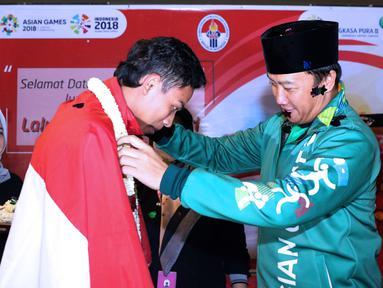Pelari muda Indonesia, Lalu Muhammad Zohri (kiri) mendapat pengalungan bunga dari Menpora Imam Nahrawi saat upacara penyambutan di pelataran Terminal 3 Bandara Soetta, Cengkareng, Tangerang, Selasa (17/7) malam. (Liputan6.com/Helmi Fithriansyah)