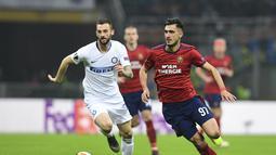 Gelandang Rapid Wien, Andrei Ivan melewati Marcelo Brozovic pada leg 2, babak 16 besar Liga Europa yang berlangsung di stadion Giuseppe Meazza, Milan, Jumat (22/2). Inter Milan menang 4-0 atas rapid Wien. (AFP/Miguel Medina)
