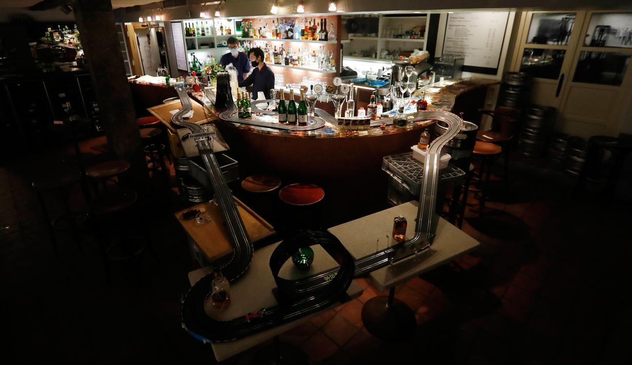 Pekerja menyiapkan minuman setelah mereka memasang lintasan mobil balap mainan di sebuah bar di Praha, Republik Ceko, 15 Oktober 2020. Area bar menjadi lintasan mobil mainan yang bisa dimanfaatkan para karyawan untuk mengusir kebosanan saat menunggu pesanan. (AP Photo/Petr David Josek)