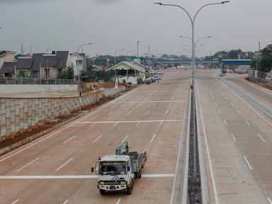 Truk melintas di dekat proyek Tol Depok-Antasari (Desari) seksi 1 di Jakarta Selatan, Selasa (17/7). BPJT Kementerian PUPR menyatakan tol seksi 1 yang menghubungkan Antasari-Brigif sepanjang 5,80 km bakal segera selesai. (Liputan6.com/Immanuel Antonius)