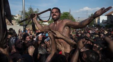 Peserta berlumuran oli saat mengikuti Festival Cascamorras di Baza, Granada, Spanyol, Kamis (6/9). Festival tradisional ini berlangsung setiap tanggal 6 September. (JORGE GUERRERO/AFP)