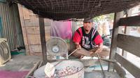 Jumadi (46), pedagang kemplang bakar Palembang, yang menjajakan jualannya di Jalan Pipa Reja Palembang Sumsel (Liputan6.com / Nefri Inge)