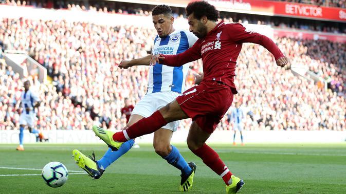 Gelandang Liverpool, Mohamed Salah mengumpan bola dari kawalan pemain Brighton and Hove Albion, Steve Sidwell saat bertanding pada lanjutan Liga Inggris di Anfield Stadium (25/8). Liverpool menang atas Brighton 1-0. (Martin Rickett/PA via AP)