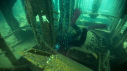 Seorang penyelam memasuki bangkai kapal karam di Pantai Ancon, pinggiran Lima, Peru, Minggu (27/3). Selain pemula, sekolah menyelam ini juga diikuti oleh penyelam berpengalaman untuk menjelajah isi kapal. (AP Photo/Rodrigo Abd)