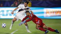 Penyerang LA Galaxy, Zlatan Ibrahimovic menggiring bola melewati kiper Orlando City, Earl Edwards Jr pada pertandingan MLS di StubHub Center di Carson, California (29/7). Ibrahimovic mencetak hattrick dipertandingan ini. (AFP Photo/Katharine Lotze)
