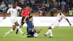 Bek Qatar, Assim Madibo, berebut bola dengan gelandang Jepang, Gaku Shibasaki, pada laga final Piala Asia 2019 di Stadion Zayed Sports City, Abu Dhabi, Jumat (1/2). Qatar menang 3-1 atas Jepang. (AFP/Karim Sahib)