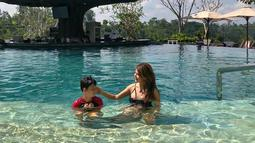 Perempuan yang kini berusia 44 tahun ini tampak sedang bermain di kolam dangkal bersama sang buah hati, Kenzou. (Liputan6.com/IG/@tamarableszynskiofficial)