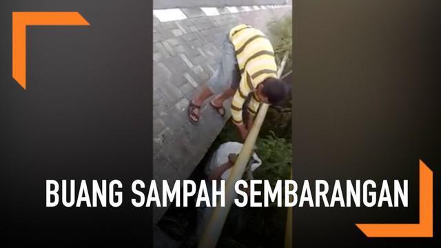 Dua orang didamprat setelah membuang satu karung sampah sembarangan. Sampah dibuang ke bawah jembatan jalanan di Bali.