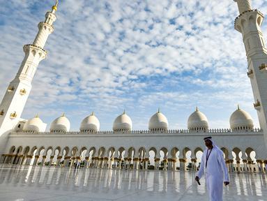Seorang pria berjalan melewati halaman Masjid Agung Sheikh Zayed di Abu Dhabi, Uni Emirat Arab. Masjid ini adalah masjid terbesar ketiga di dunia setelah masjid di Mekkah dan Madinnah. (Photo by Vincenzo PINTO / AFP)