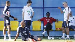 Pelatih Didier Deschamps berbincang santai dengan pemain Prancis sebelum sesi latihan di Glebovets, Rusia, (12/7/2018). Latihan tersebut sebagai persiapan Prancis melawan Kroasia pada Final Piala Dunia 2018. (AP/David Vincent)