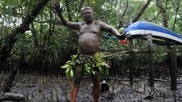 Seorang pria Bali menari dengan berlumur lumpur ditubuhnya saat mengikuti tradisi Mebuug-buugan di desa Kedonganan, Denpasar, Bali (10/3). Mebuug-buugan bertujuan untuk menetralkan sifat-sifat buruk usai hari raya Nyepi. (AFP/Sonny Tumbelaka)