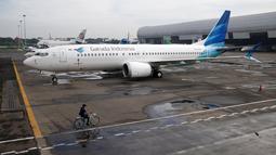 Seorang pegawai mengendarai sepeda melewati pesawat Boeing 737 Max 8 Garuda Indonesia yang terparkir di Bandara Soekarno Hatta, Tangerang, Rabu (13/3). Pemerintah masih mengecek Boeing 737 Max 8 yang terdapat di Indonesia. (REUTERS/Willy Kurniawan)