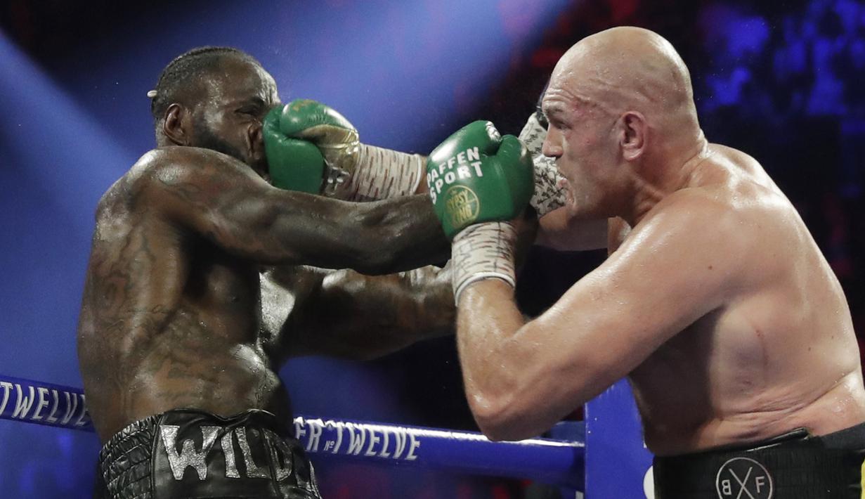 Petinju Inggris Tyson Fury melancarkan pukulan ke arah wajah petinju AS Deontay Wilder pada pertandingan tinju kelas berat WBC di Las Vegas (23/2/2020). Tyson Fury berhasil memenangkan pertarungan di ronde ketujuh. (AP Photo/Isaac Brekken)