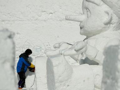 Seorang seniman mengukir patung es raksasa di Snow Land, PyeongChang, Korea Selatan, Minggu (4/2). Hal ini dilakukan untuk menyambut Olimpiade Musim Dingin PyeongChang 2018. (AP Photo/Charlie Riedel)