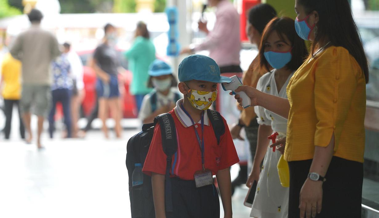 Seorang siswa diukur suhu tubuhnya di pintu masuk sebuah sekolah di Bangkok, Thailand (1/7/2020). Sekolah-sekolah di Thailand telah dibuka kembali pada Rabu (1/7). (Xinhua/Rachen Sageamsak)