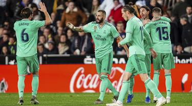 Penyerang Real Madrid, Karim Benzema (kedua kiri) berselebrasi dengan rekan-rekannya usai mencetak gol ke gawang Valencia pada pertandingan lanjutan La Liga Spanyol di Stadion Mestalla (15/12/2019). Benzema mencetak gol pada menit (90+5) dan membuyarkan kemenangan Valencia. (AP Photo/Alberto Saiz)