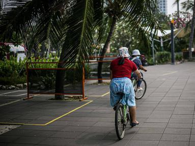 Pengunjung bersepeda di kawasan Taman Impian Jaya Ancol, Jakarta, Sabtu (11/10/2021). Kawasan rekreasi Taman Impian Jaya Ancol menjadi salah satu dari 20 destinasi wisata yang direkomendasikan beroperasi kembali dalam uji coba pembukaan kawasan rekreasi. (Liputan6.com/Faizal Fanani)