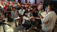 Calon peserta tax amnesty mendengarkan pengarahan petugas di kantor pusat Ditjen Pajak, Jakarta, Minggu (25/9). Pendaftaran akhir pekan dibuka guna mengakomodir wajib pajak yang tak sempat mendaftar di hari kerja. (Liputan6.com/Fery Pradolo)